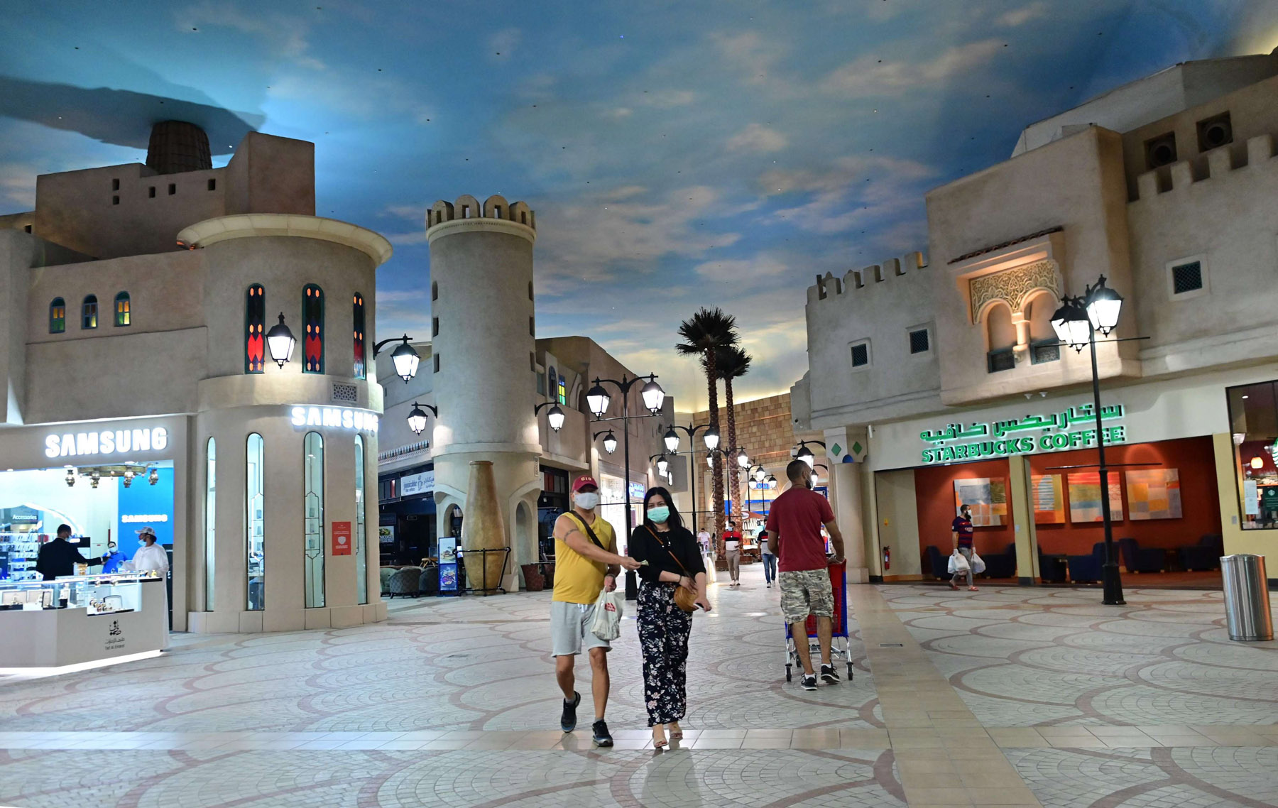 Customer wearing protective masks walk in nearly empty shopping mall in Dubai. (AFP)