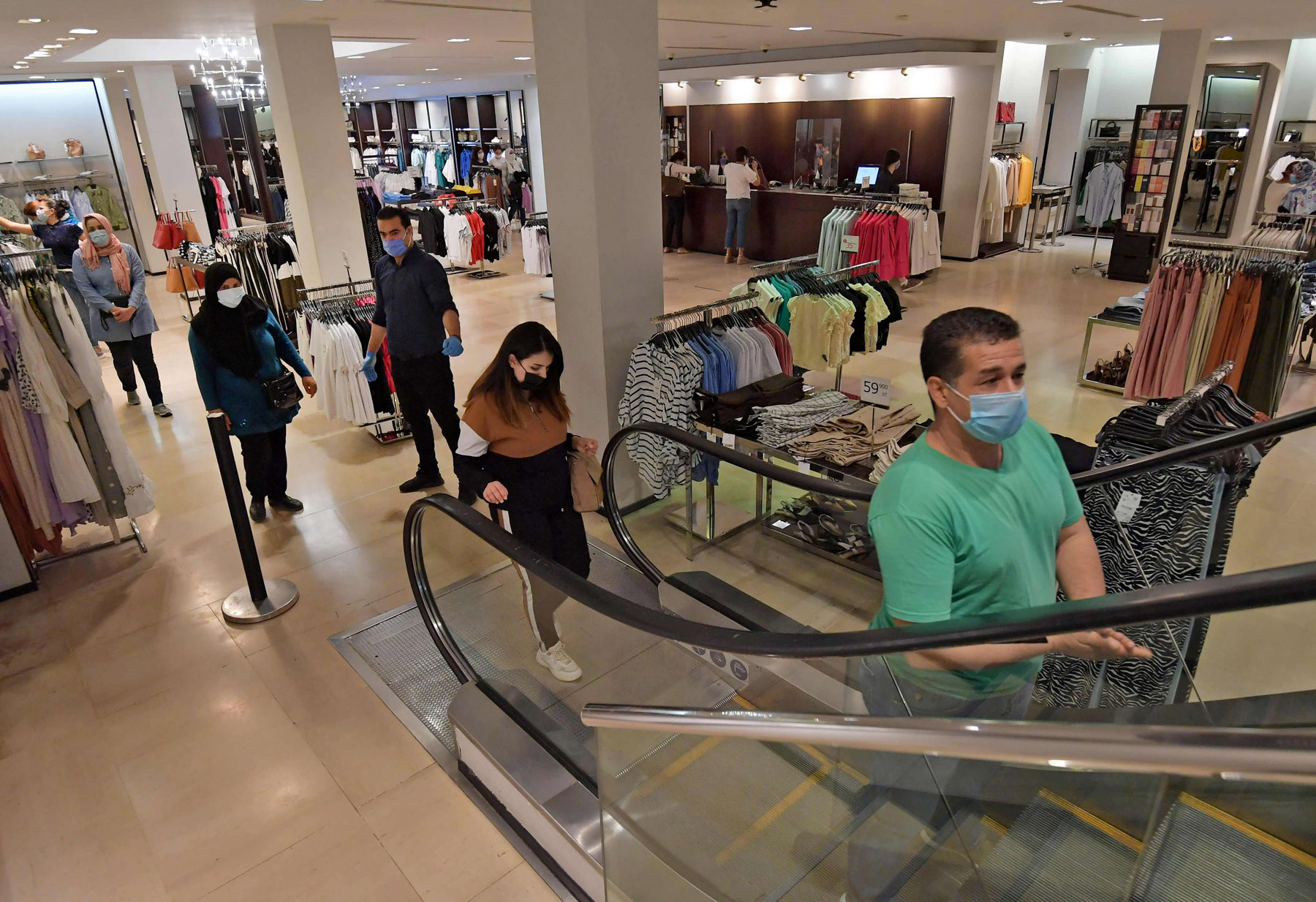 Shoppers, wearing protective face masks, observe a safe distance at a clothing store in the Tunisian capital Tunis. (AFP)