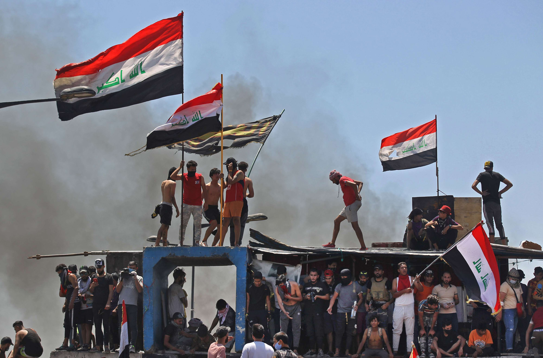 Iraqi protesters raise national flags as they clash with security forces on Al-Jumhuriyah bridge in the capital Baghdad. (AFP)
