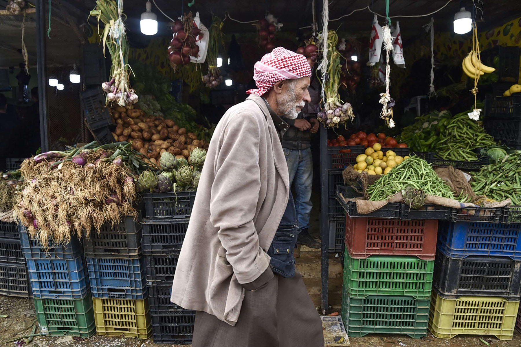 An Algerian man walks by a greengrocer's stall in a market of the Khraicia district, 20km south of the capital. (AFP)
