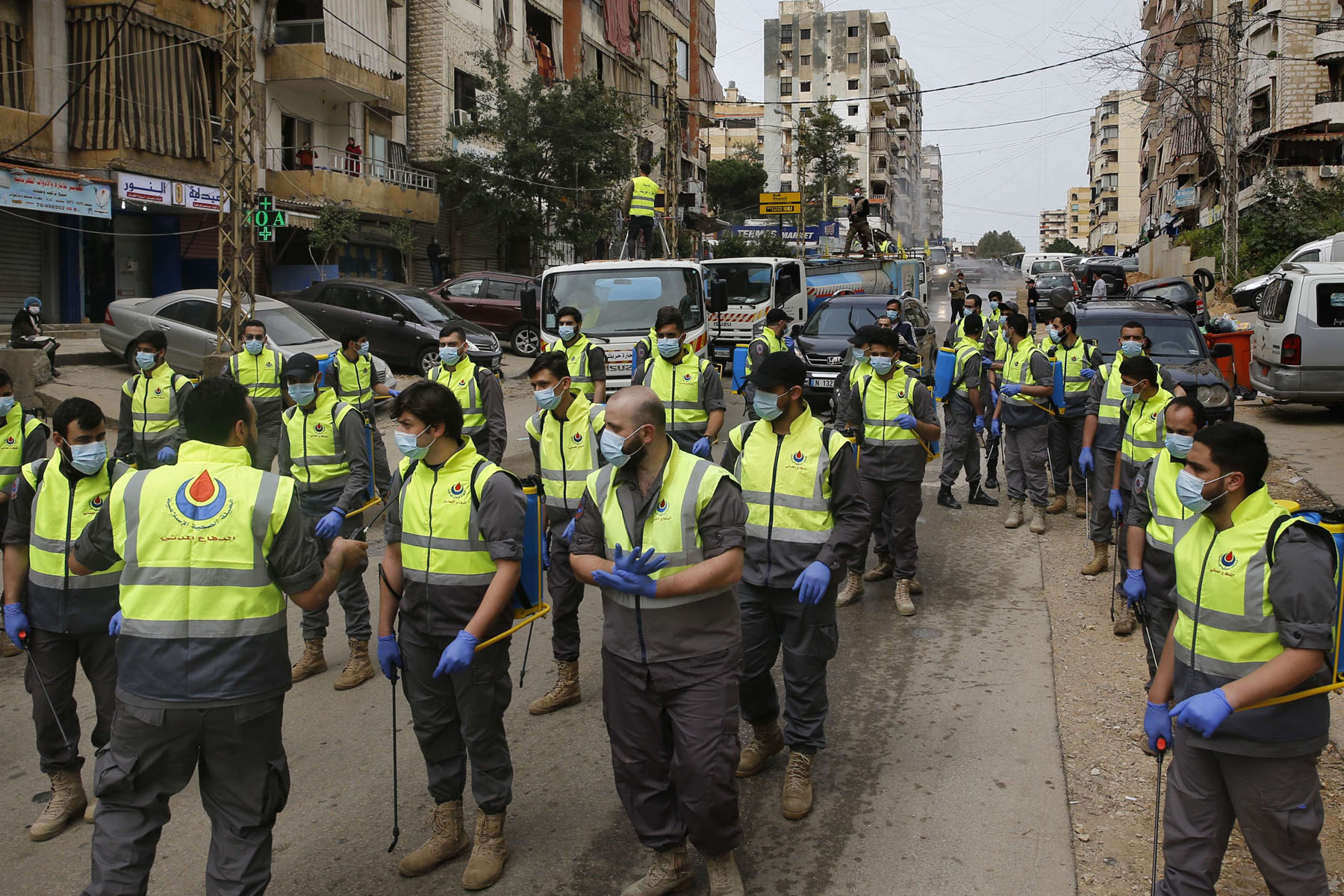 Members of the Islamic Health Society, an arm of the Iran-backed militant Hezbollah group prepare to spray disinfectant as a precaution against the coronavirus, in a southern suburb of Beirut. (AP)