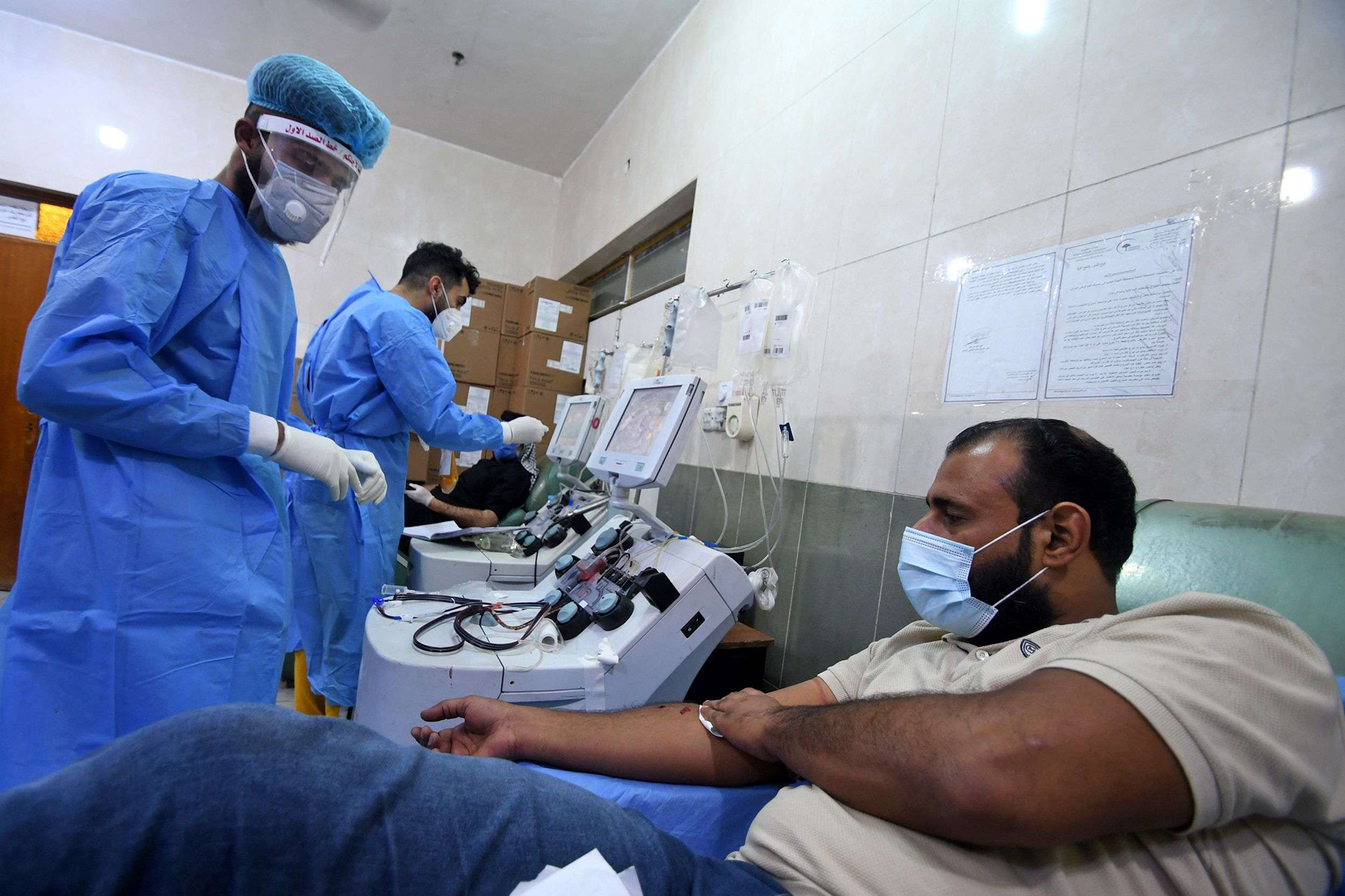 Iraqi phlebotomists draw blood plasma from recovered COVID-19 patients at the blood bank of Iraq's southern city of Nasiriyah in Dhi Qar province. (AFP)