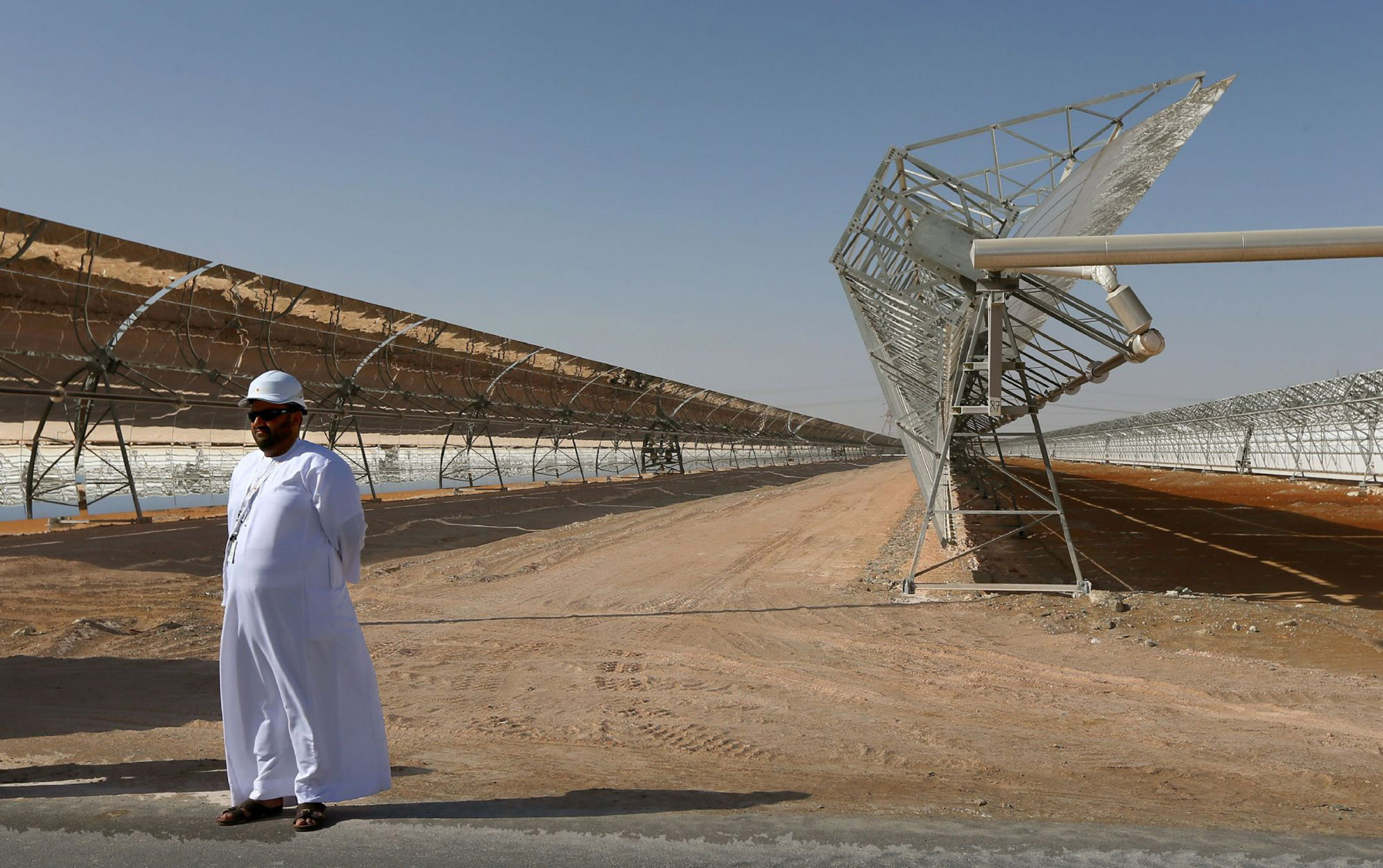 An Emirati man stands in front of rows of parabolic shaped mirrors at the Shams 1, Concentrated Solar power (CSP) plant, in al-Gharibiyah district on the outskirts of Abu Dhabi. (AFP)
