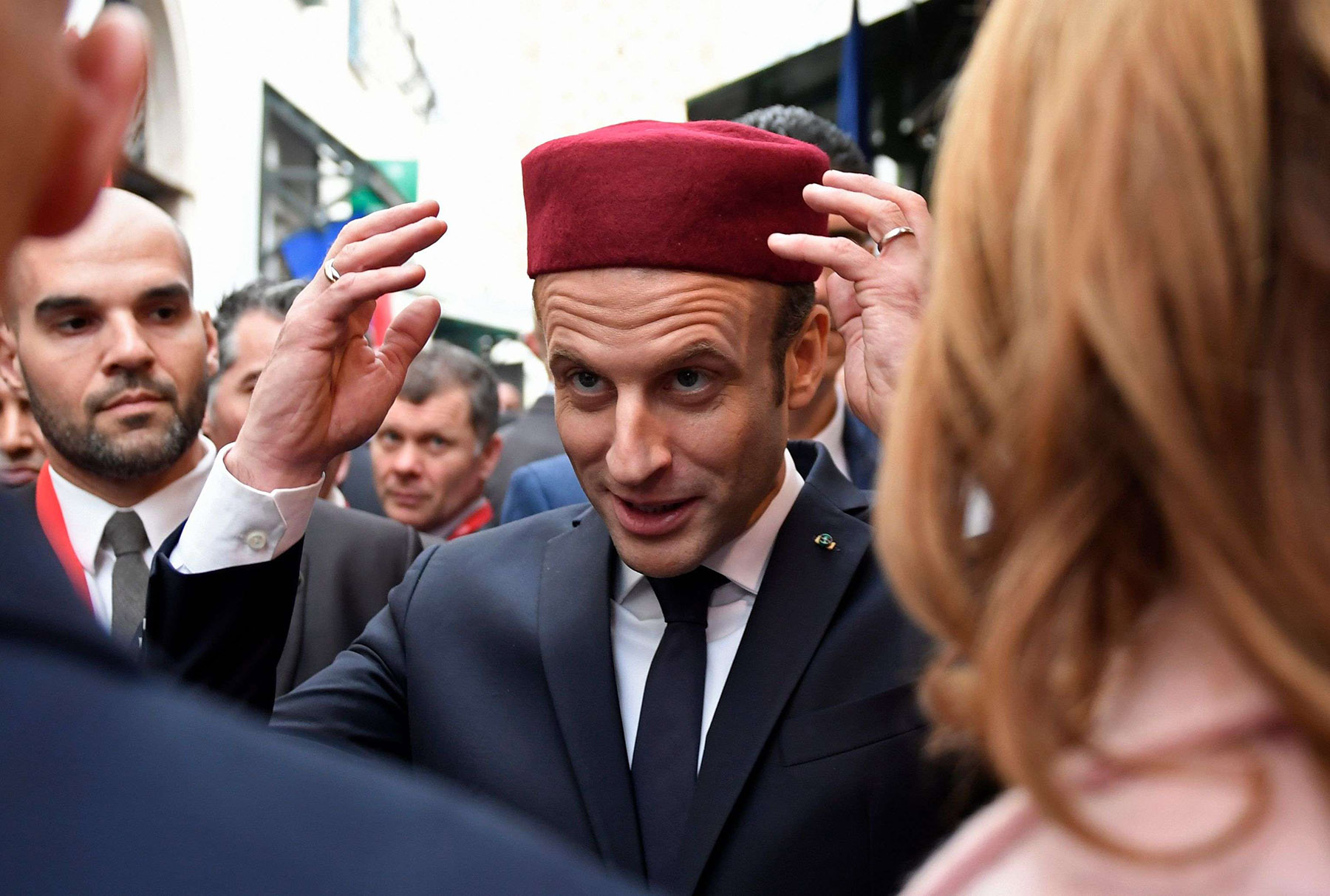 French President Emmanuel Macron (C) tries on a chechia during his tour of the Medina of Tunis in February 2018, during Macron's first state visit to the North African country. (AFP)