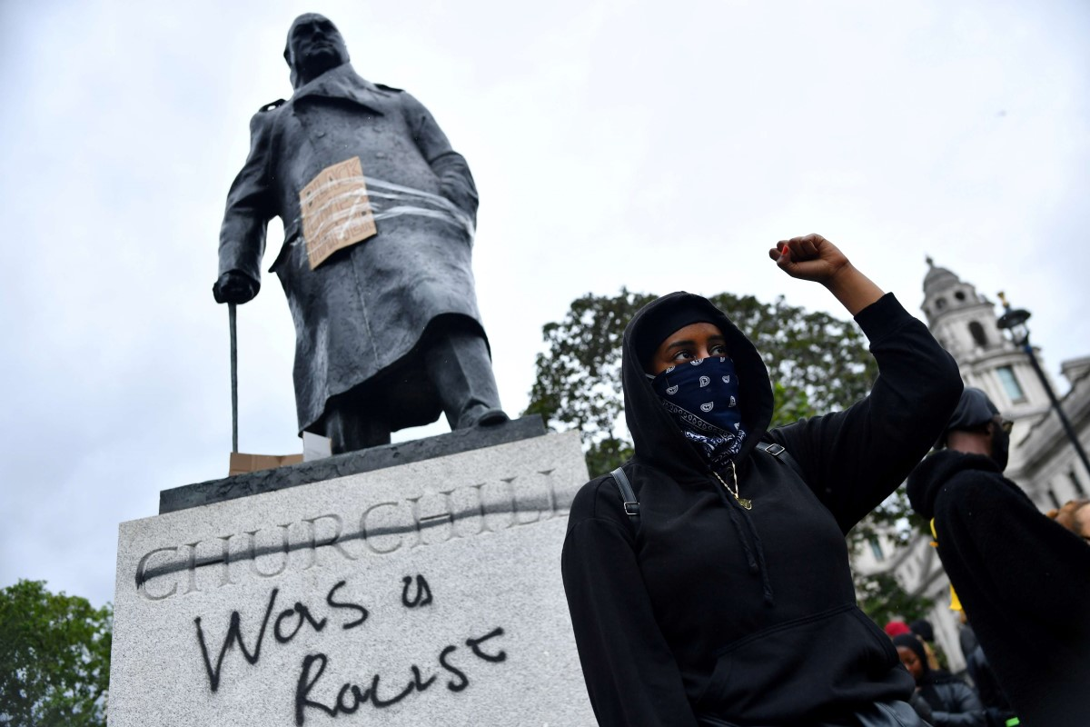 A demonstrator reacts infront of graffiti on a statue of Winston Churchill in Parliament Square during a Black Lives Matter protest in London. (AFP)