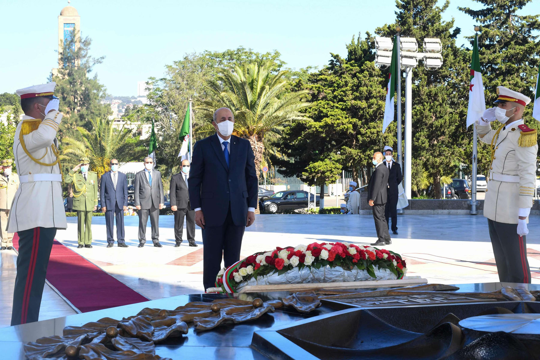 Algeria's President Abdelmajid Tebboune observes a moment of silence during a ceremony to lay to rest the remains of 24 resistance fighters, returned from Paris after more than a century and a half. (AFP)