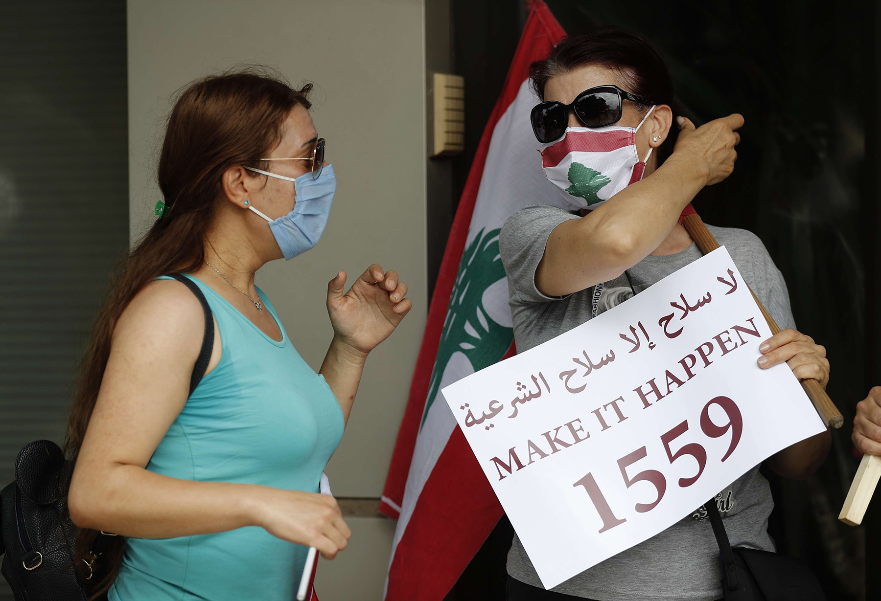 A Lebanese protester holds a placard endorsing UN Resolution 1559, which calls for the disarmament of all Lebanese and non-Lebanese militias, during a sit-in against Hezbollah and Iran, July 14, in Beirut. (AFP)