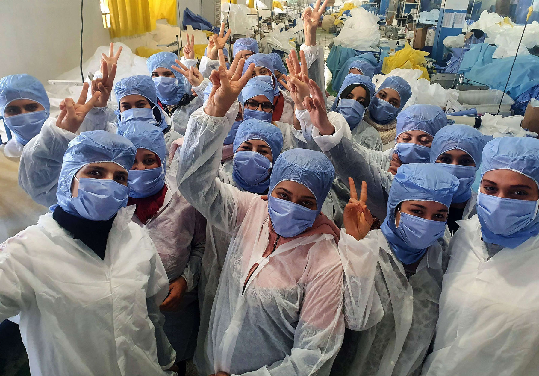 Tunisian women cheering as they work on the production of medical masks in the company's factory in the central city of Kairouan, last March.  (AFP)