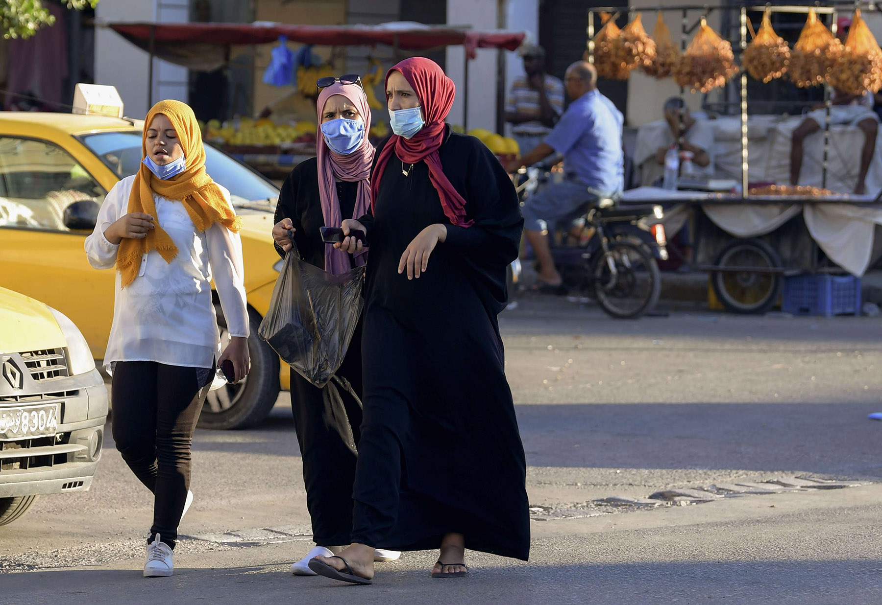 Tunisian women wear face masks for protection against the novel coronavirus at a market in the southwestern Tunisian town of Gabes on August 26. (AFP)