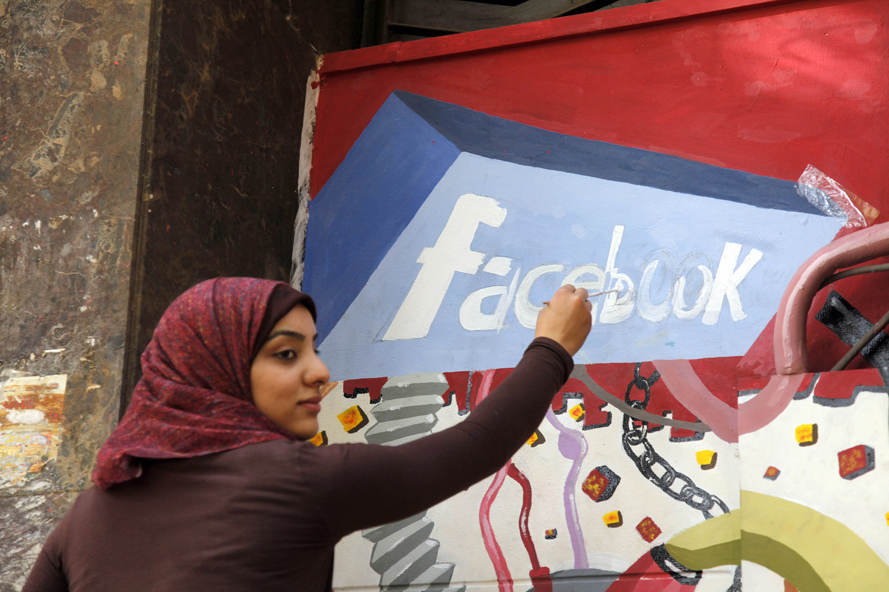 A file photo shows an art student from the University of Helwan painting the Facebook logo on a mural commemorating the uprising that overthrew Hosni Mubarak in the Zamalek neighbourhood of Cairo, Egypt. (AFP)