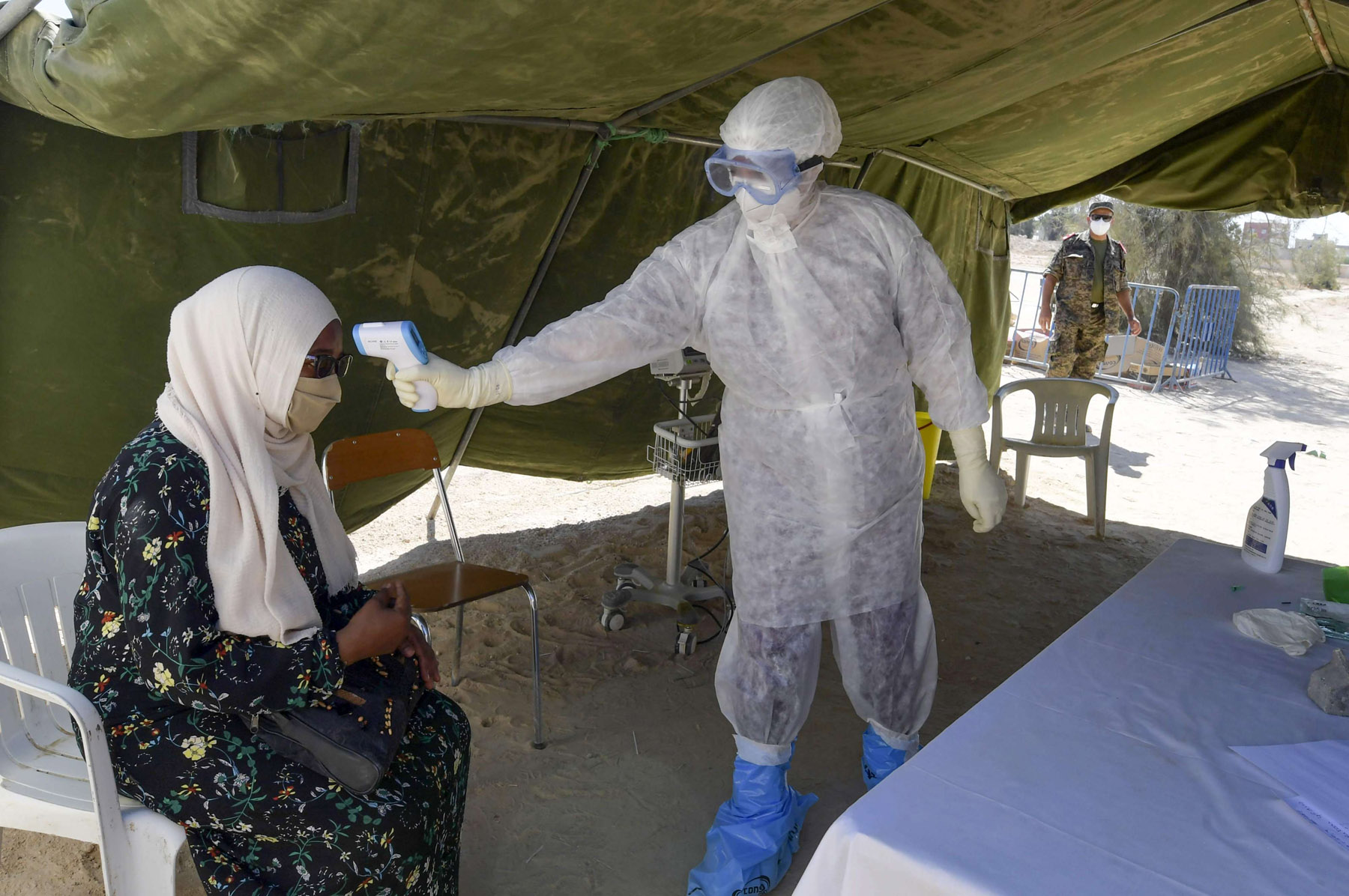A nurse checks a woman's temperature before a covid-19 test at a military mobile hospital in the town of El-Hamma, in Tunisia's southwestern Gabes governorate, on August 26. (AFP)
