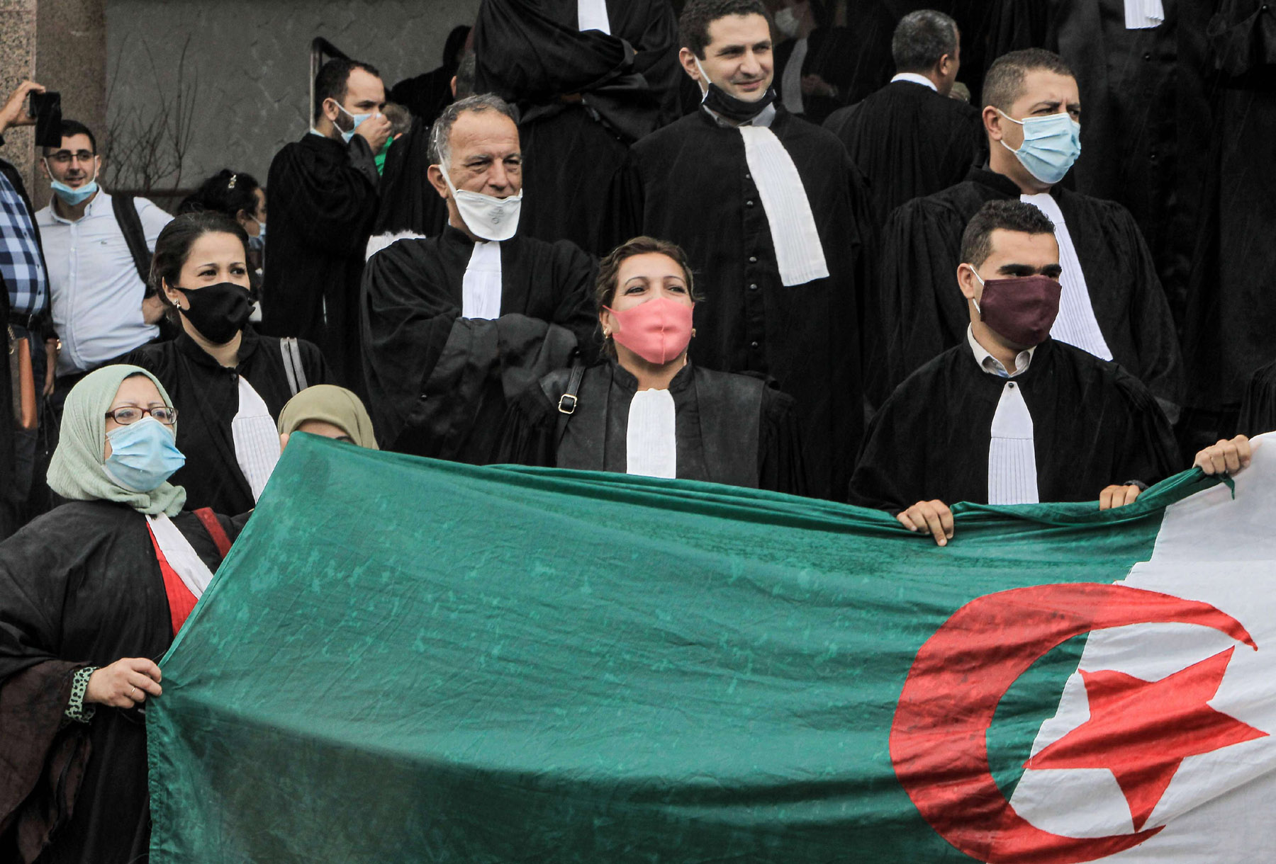 Lawyers chant slogans and wave an Algerian national flag as they demonstrate outside the Court of Algiers on September 27. (AFP)