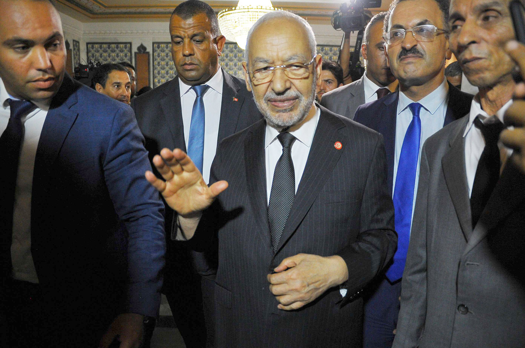 A file picture of Ennahda chief Rached Ghannouchi, surrounded by bodyguards and aides. (AFP)