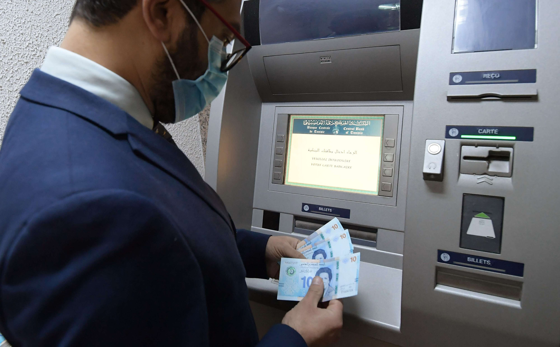 A Tunisian man retrieves bank notes from an ATM in the capital Tunis. (AFP)