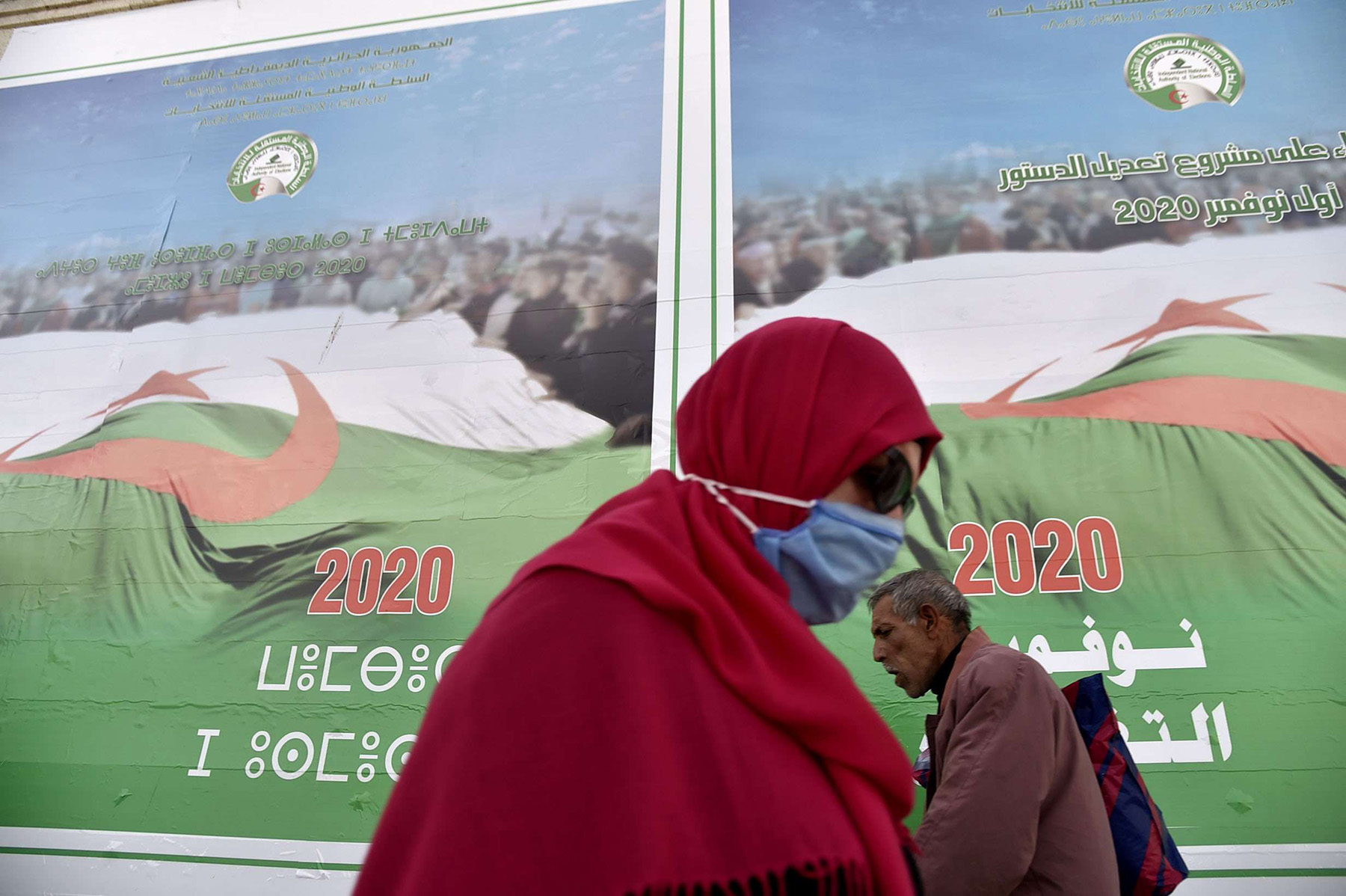 Algerians walk past campaign billboards ahead of the November referendum, on October 22, in Algiers. (AFP)