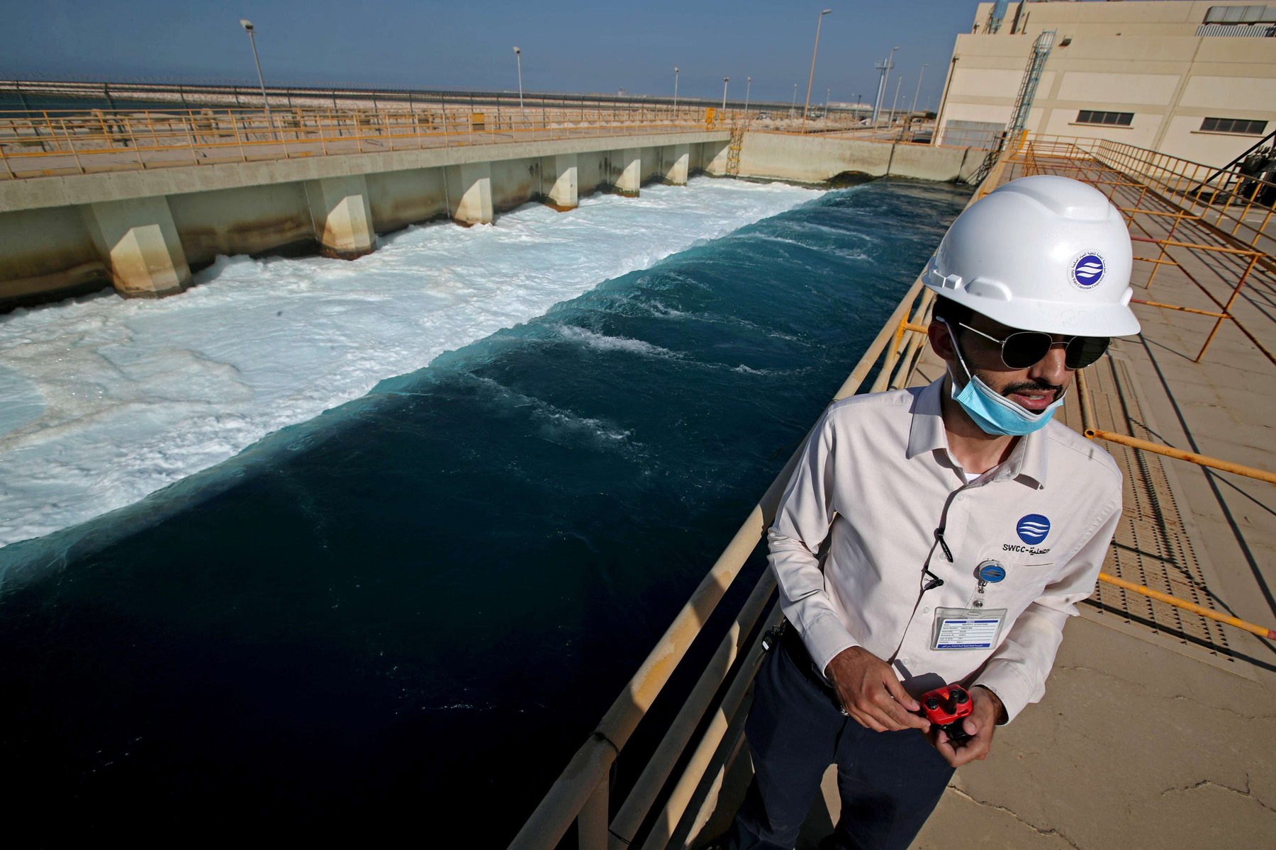 An employee stands next to a waste water collection pool at the Saline Water Conversion Corporation's Ras Al-Khair Power and Desalination Plant at Ras Al-Khair, Saudi Arabia. REUTERS