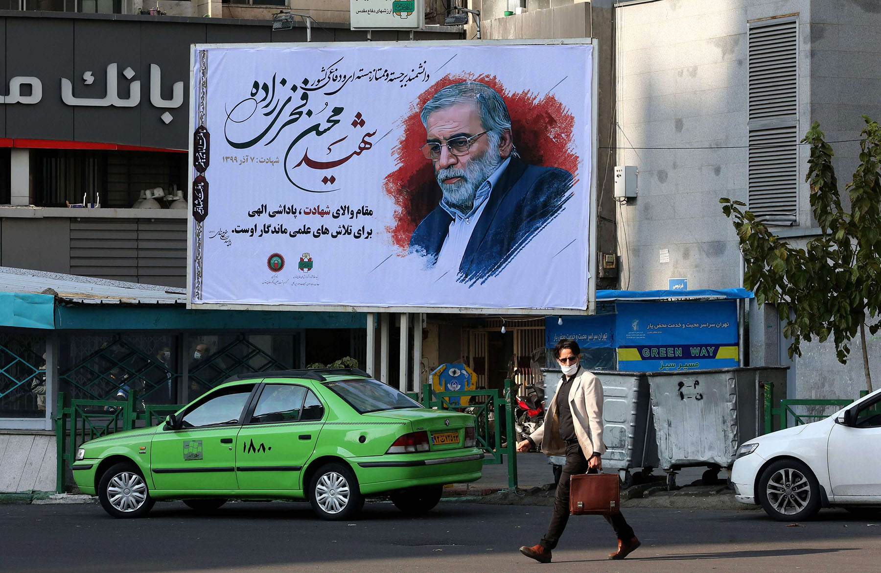 An Iranian man walks by a billboard of slain Iranian nuclear scientist Mohsen Fakhrizadeh in Tehran, on November 30, 2020. (AFP)