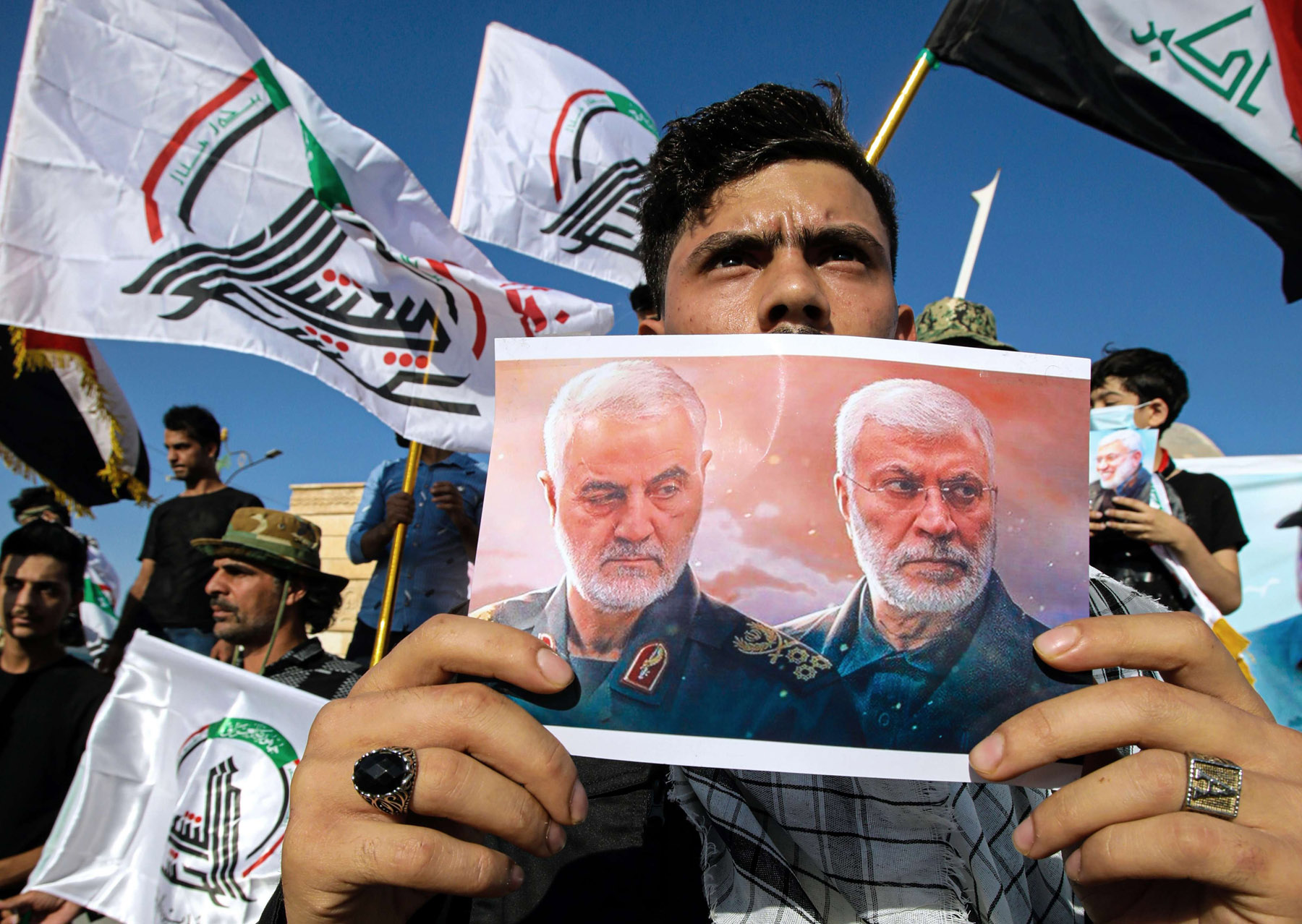 A supporter of pro-Iran militias holds a poster of Iranian General Qassem Soleimani and Shia commander Abu Mahdi al-Muhandis during a protest in Basra, Iraq. (AP)