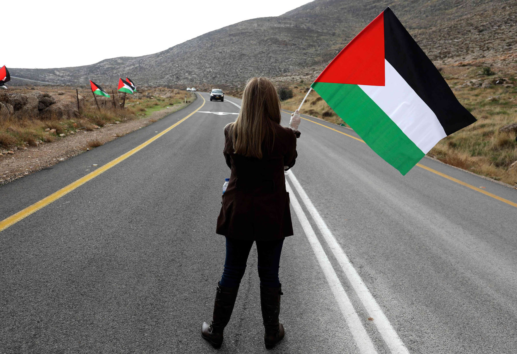 A Palestinian woman stands in middle of a road during a demonstration against Jewish settlements in the village Kafr Malik in the Israeli-occupied West Bank, on November 20, 2020. AFP
