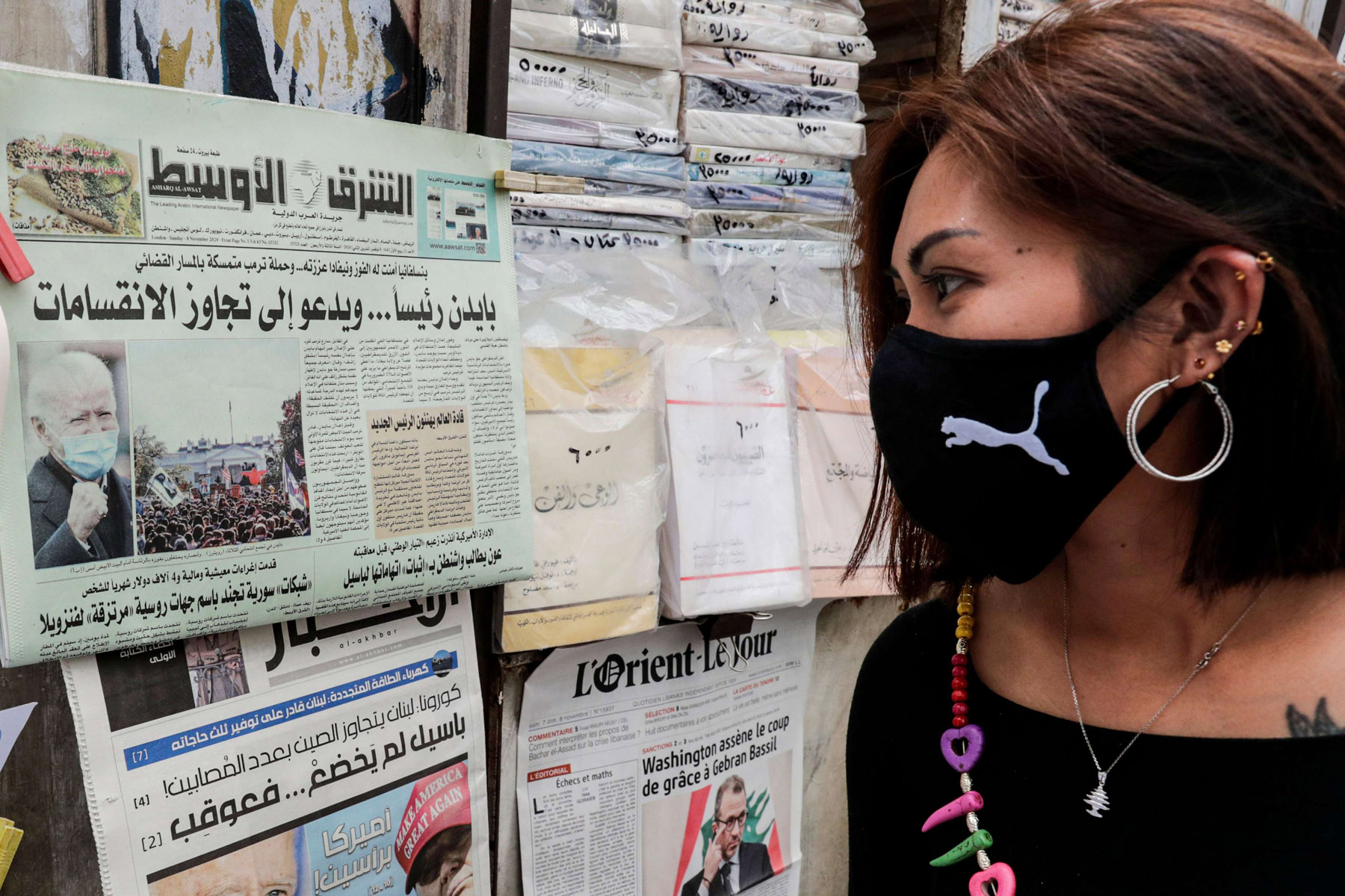 A woman looks at newspaper headlines after the 2020 US election results, at a news stand in Beirut on November 8, 2020.  AFP