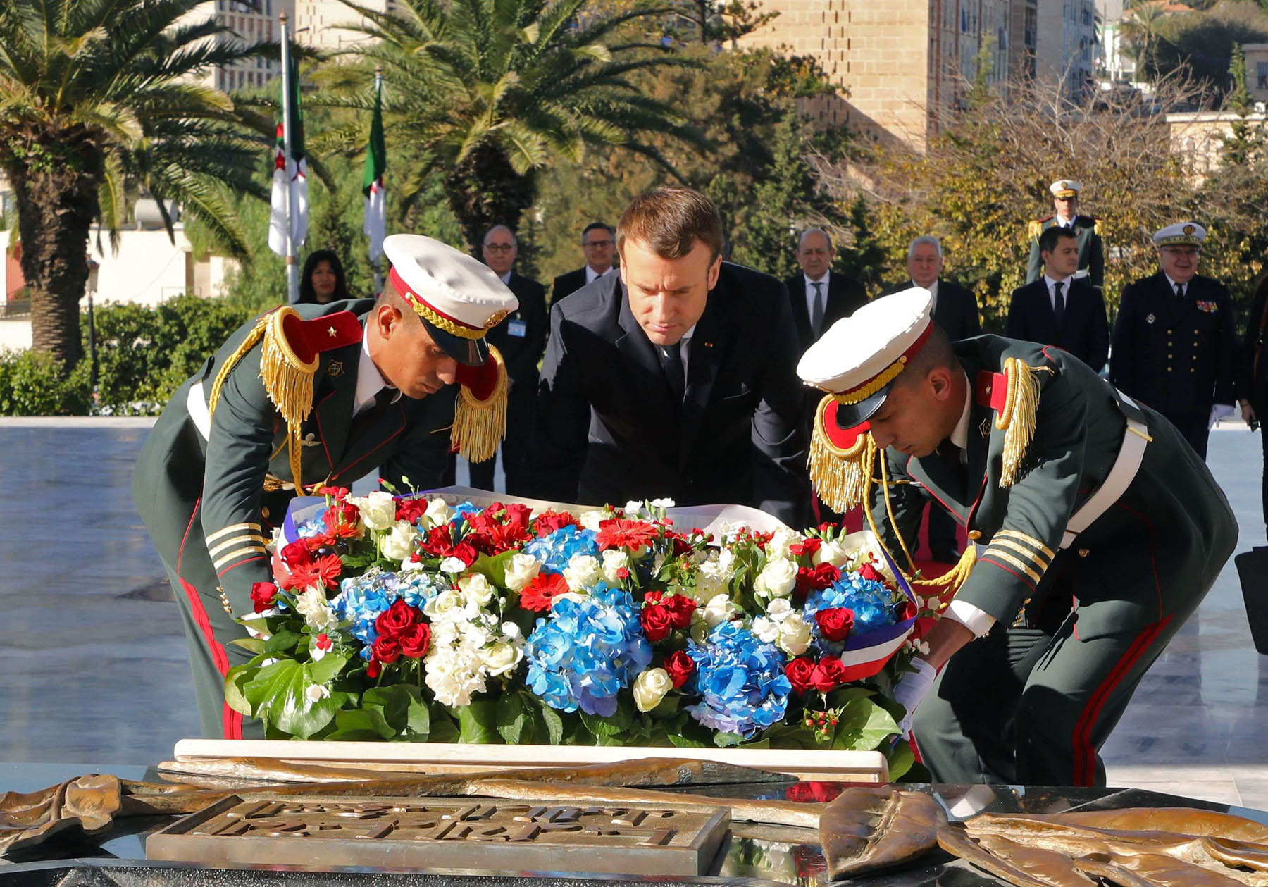 French President Emmanuel Macron (C) lays a wreath at the Martyrs' Memorial in the Algerian capital Algiers during his visit on December 6, 2017. (AFP)