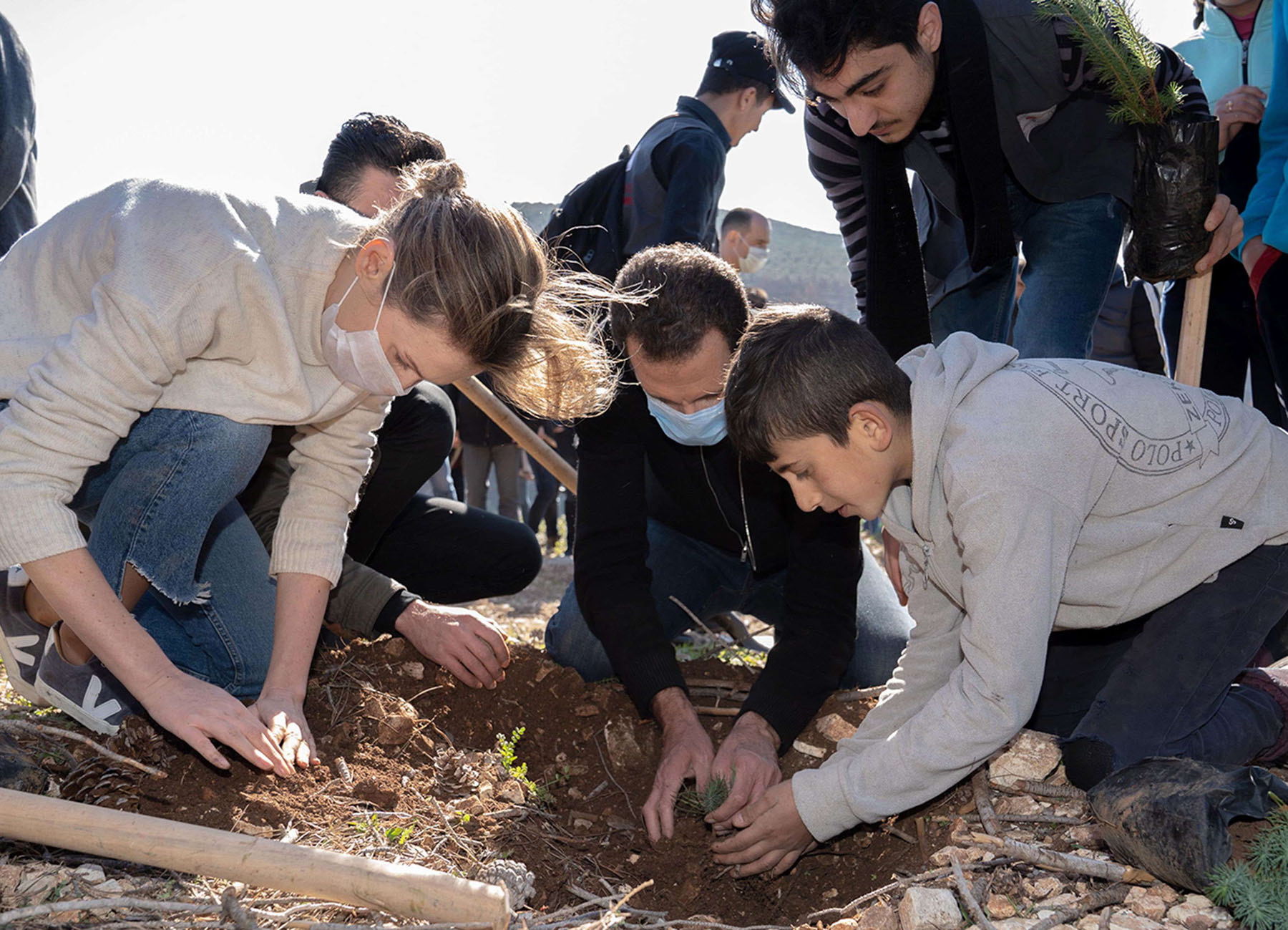 Syrian President Bashar al-Assad (C), his wife Asma (L) and their children during the afforestation of Harsh al-Tufaha (Apple Forest) area in al-Drekish countryside in western Syria. (AFP)