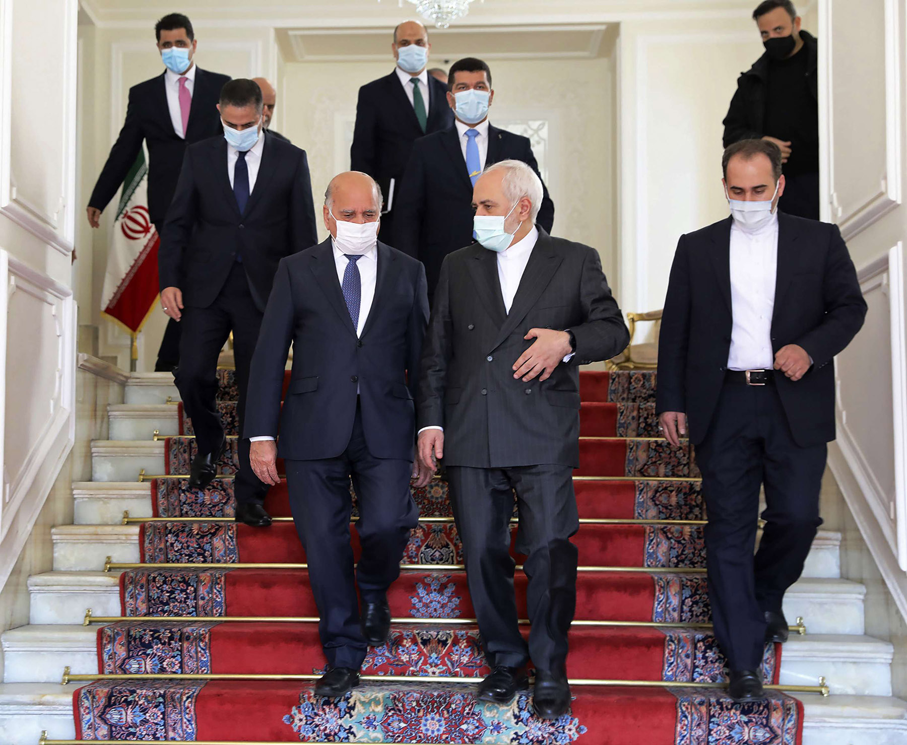 Iranian Foreign Minister Mohammad Javad Zarif, center right, and his Iraqi counterpart Fuad Hussein, center left, arrive for a meeting in Tehran, Iran, Feb. 3, 2021. (AP)
