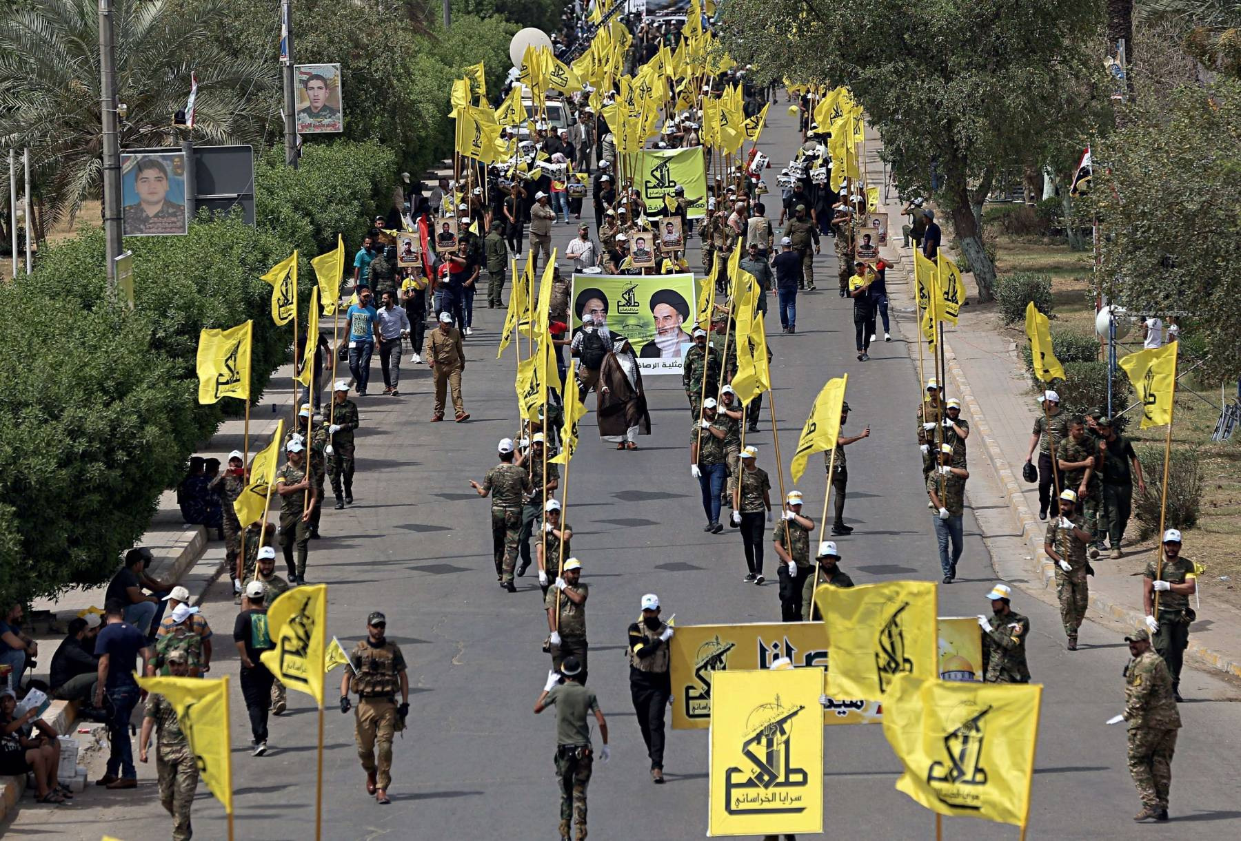 "A file picture shows Iraqi Popular Mobilization Forces marching and holding flag and posters of Iraqi and Iranian Shia spiritual leaders during ""al-Quds"" or Jerusalem Day, in Baghdad, Iraq. (AP)"