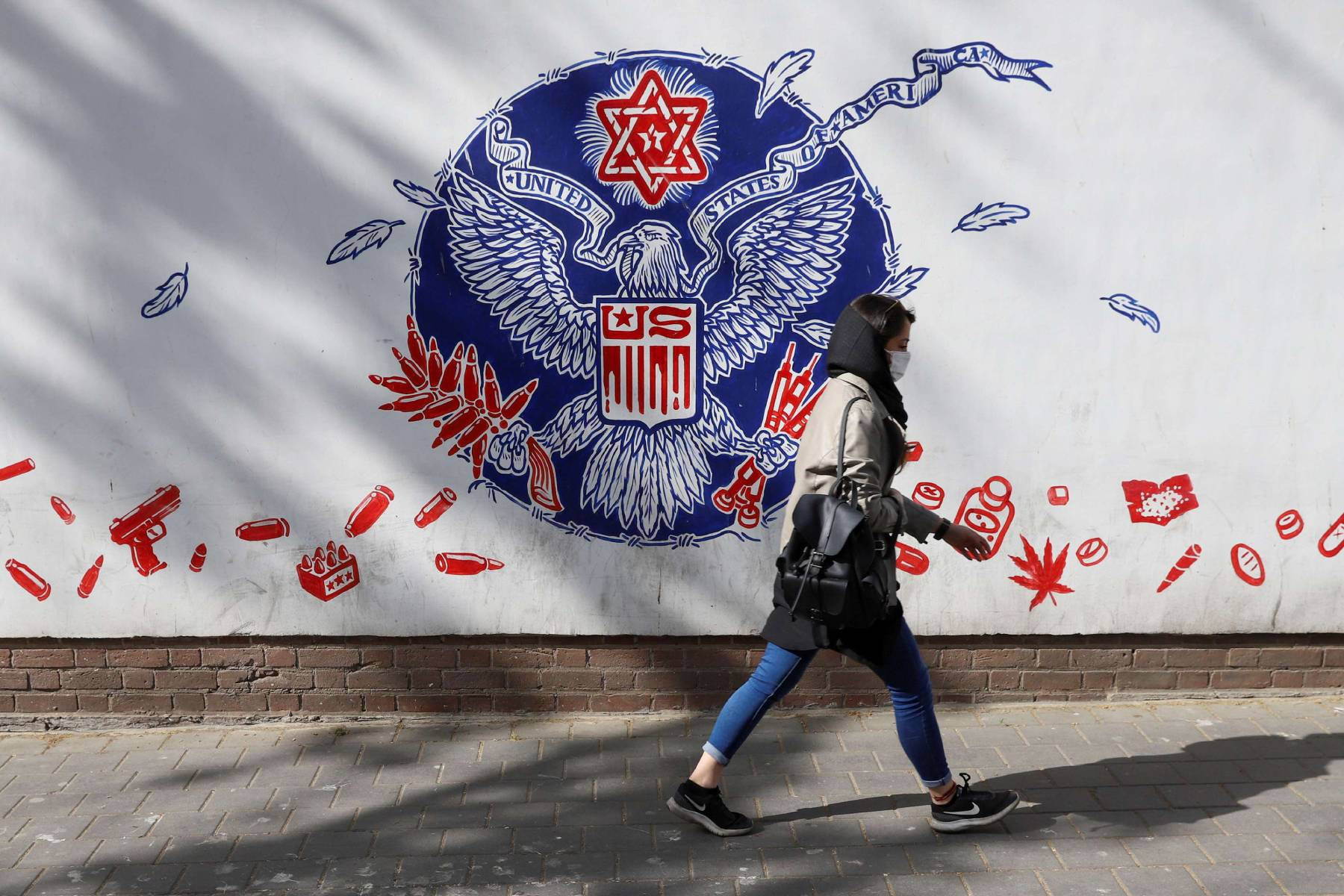 An Iranian woman walks past a wall of the former US Embassy, with an anti-America mural on it, in Tehran. (AFP)