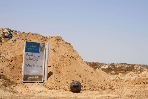 A sign indicates a communal cemetary , where African migrants, whose bodies were recovered on the Tunisian coast, are buried in El Ketif near the eastern coastal city of Zarzis, on July 16, 2019. (AFP)