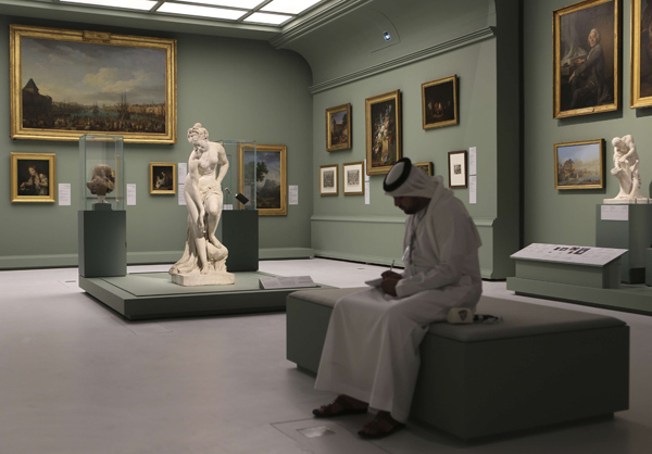 An Emirati visitor sits next to the Bather, also called Venus statue by Christophe-Gabriel Allegrain, 1710-1795, at the Louvre Museum in Abu Dhabi. (AFP)