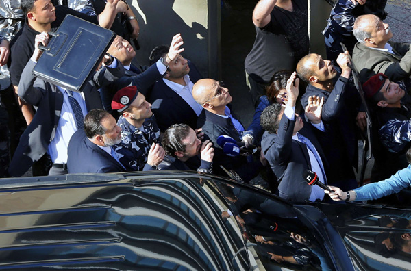 Bodyguards protect then-Lebanese Prime Minister Saad Hariri, center left, from water bottles thrown by demonstrators, in downtown Beirut, Lebanon. (AP)