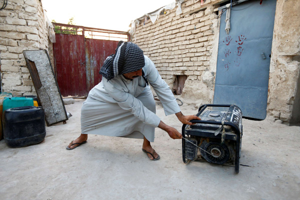 An Iraqi man tries to run his personal electrical generator at home, after continuous power outages in the holy city of Najaf, Iraq. (AP)