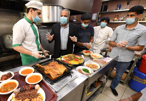 Staff wearing face masks inside a restaurant in Dubai on May 26, 2020 as the Gulf emirate moved to ease their lockdown measures amid the coronavirus pandemic. (AFP)