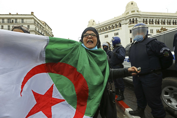 A woman holds an Algerian flag as Algerians demonstrate in Algiers to mark the second anniversary of the Hirak movement, Feb. 22, 2021. (AP)