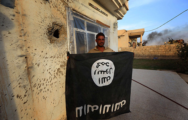A 2016 file photo shows a member of the Iraqi  holding  an Islamic State (ISIS) group flag, upside down, in the village of Jarif, some 45 kilometres south of Mosul. (AFP)