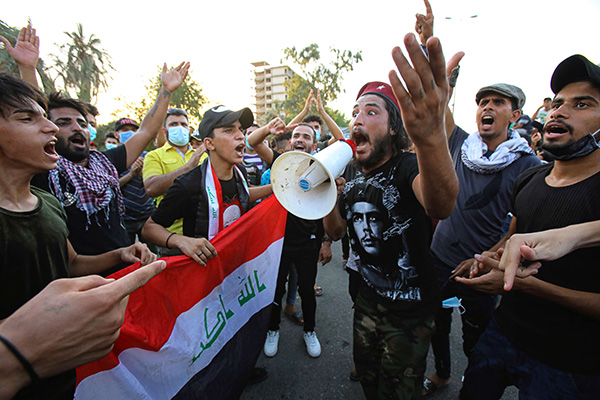 Anti-government protesters gather for a demonstration demanding better public services and against corruption outside the provincial council building, in Basra, Iraq, Friday, Aug. 7, 2020. (AP)