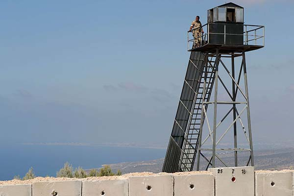 Lebanese soldiers on a watch tower along a new wall on the Israeli-Lebanese border. (AFP)