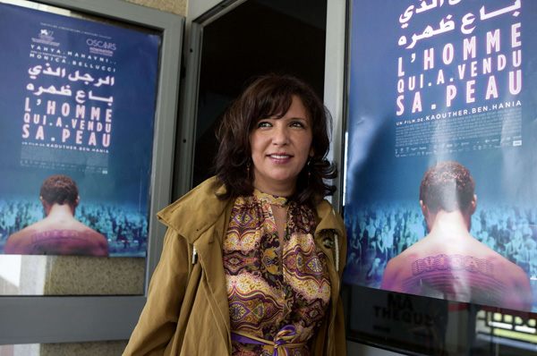 "Tunisian director and screenwriter Kaouther Ben Henia, poses for a picture in front of the poster of her film ""The man who sold his skin"" during its first screening in the country, in the capital Tunis, on March 30, 2021. (AFP)"