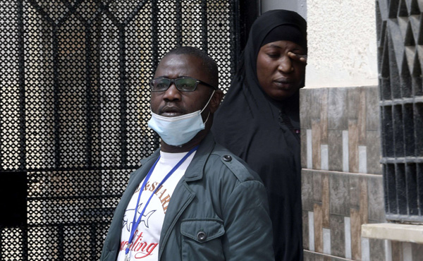 Oumar Coulibaly, head of the association of Ivorians in the Tunisian city of Sfax, stands with African migrant in the coastal city. (AFP)