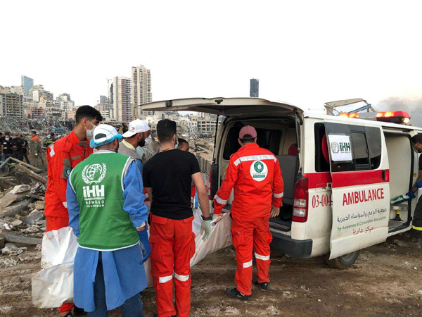 Members of Turkey's Humanitarian Relief Foundation (IHH) help local medics at the site of blast in Beirut's port area, August 5. (REUTERS)