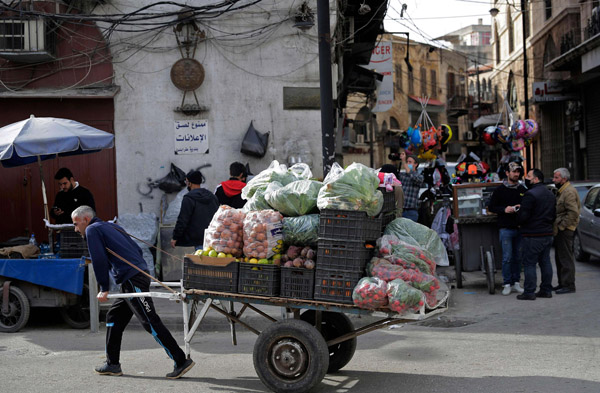 An ambulant vendor pulls his handcart in the Lebanese coastal city of Tripoli, north of Beirut, on January 26, 2021. (AFP)