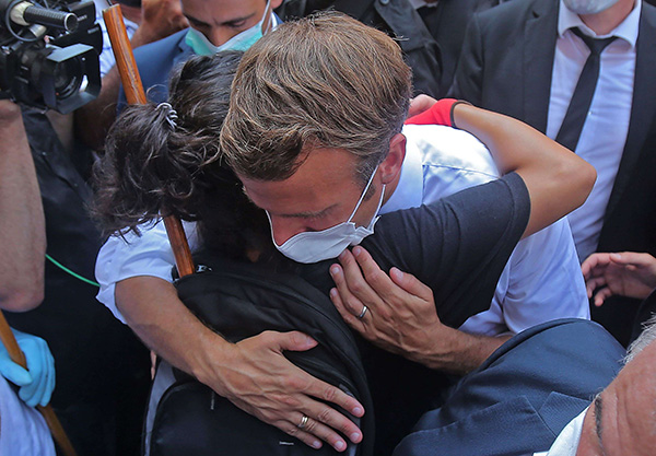 A Lebanese youth hugs French President Emmanuel Macron during a visit to the Gemmayzeh neighborhood, which has suffered extensive damage due to a massive explosion in the Lebanese capital, on August 6. (AFP)