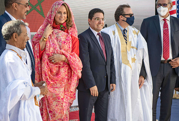 Moroccan Foreign Minister Nasser Bourita (C) and US Assistant Secretary of State for Near Eastern Affairs David Schenker — who is wearing a traditional Sahrawi dress — (centre-R) pose for a picture after their meeting in Dakhla. (AP)