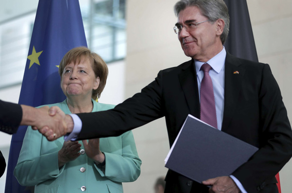 A file picture shows Iraq's former Electricity Minister Luay Al-Khateeb shaking hands with the CEO of Siemens, Joe Kaeser, as.German Chancellor Angela Merkel, left, applauds. (DPA)