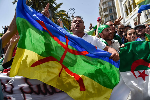 Sore issue. Algerian protesters wave the Amazigh (C) and national flags during the Hirak demonstrastions in the capital Algiers, last June. (AFP)