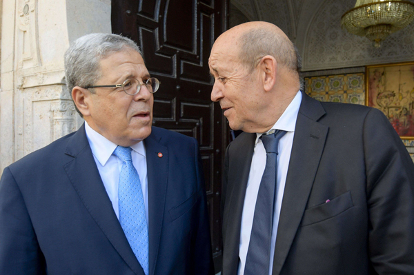 Tunisia's Foreign Minister Othman Jerandi speaks with his French counterpart Jean Yves Le Drian (R) in Tunis on October 22. (AFP)
