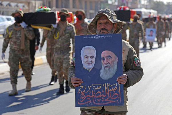 PMF member carries portraits of slain Iranian  commander Qasem Soleimani and Ayatollah Ali Sistani during a  procession on the anniversary of US strikes on bases of Hezbollah brigades near Al-Qaim.  (AFP)