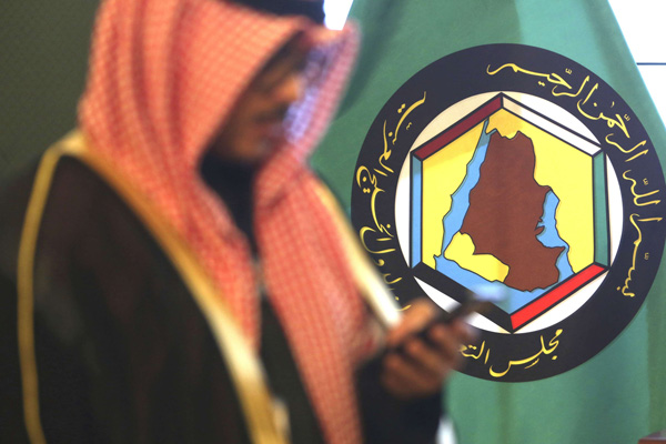 A man looks at his mobile phone in front of the flag of the Gulf Cooperation Council (GCC) in Kuwait City, Kuwait. (AP)