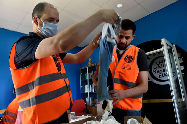 Algerian volunteers prepare parcels of clothing to be distributed to needy families, ahead of Eid al-Fitr . (AFP)